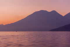 Lake Atitlan and volcanoes and boat in the morning Royalty Free Stock Photos