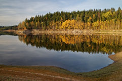 Lake in autumn landscape, on the opposite bank of rocks and forest Royalty Free Stock Photography