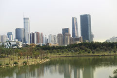 The lake is on a background of green hills and skyscrapers. Beautiful cityscape. Stock Photography