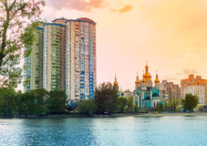 A lake on the background of high-rise buildings and churches at sunset. Ukraine, Kiev, Lake Telbin Royalty Free Stock Photo