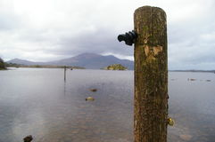 Lake background with a wooden pol. E in the front and a mountain at the back of the lake Stock Image