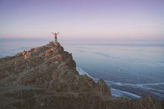 Free Lake Baikal At Winter. Man Standing On A Edge Of Cliff And Looking At Frozen Baikal Lake. Royalty Free Stock Photography - 165810177