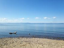 Lake Baikal, the blue expanse of water and small stones on the shore, a calm landscape. The cleanest lake on Earth, the natural reservoir of clean drinking stock images