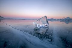 Lake Baikal is covered with ice and snow, strong cold, thick clear blue ice. Icicles hang from the rocks. Lake Baikal is a frosty royalty free stock photography
