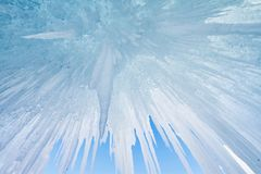 Lake Baikal is covered with ice and snow, strong cold, thick clear blue ice. Icicles hang from the rocks. Lake Baikal is a frosty royalty free stock image
