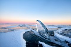 Lake Baikal is covered with ice and snow, strong cold, thick clear blue ice. Icicles hang from the rocks. Lake Baikal is a frosty stock photo
