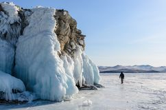 Lake Baikal is covered with ice and snow, strong cold, thick clear blue ice. Icicles hang from the rocks. Lake Baikal is a frosty royalty free stock photo