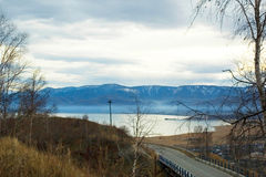 Lake Baikal. Descent to the lake Baikal on the background of the blue mountains and the grey sky Stock Photos