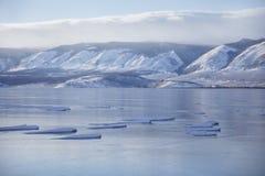 Lake Baikal ice. Mountain shore. Winter landscape. Lake Baikal ice. Mountain shore in the distance. Winter landscape Stock Photos