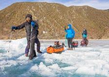 Lake Baikal Ryssland - mars 24, 2016: Männen släpade isen sl Arkivfoto