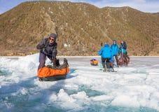Lake Baikal Ryssland - mars 24, 2016: Männen släpade isen sl Royaltyfri Fotografi