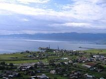 Lake Baikal. A small village on the shore. View from above. In a blue cloudy light royalty free stock photos