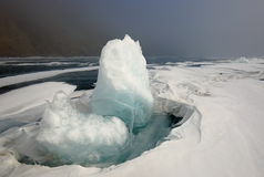 Lake Baikal in winter. Ice block on the ice field of the lake in the background fog Royalty Free Stock Images