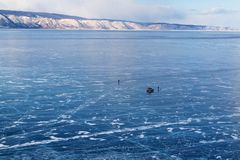 Lake Baikal in winter season. Cracks on the smooth surface of the ice with car and people on ice. Olkhon Island. Winter tourism co Stock Photo