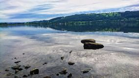 Lake Bala in Wales. Photograph of Lake Bala in Wales with Stones and Rocks with countryside and blue sky Royalty Free Stock Image