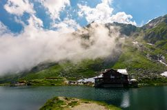 Lake Balea of Fagaras mountains. Lovely summer landscape with low clouds around the peak Stock Photos