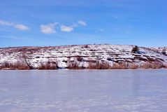 Lake bank covered with ice, yellow reeds line and pine on hill, blue cloudy sky. Background stock images