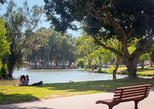 Lake, bench, girls with dog, and relax in Yarkon Park, Tel Aviv, Israel Royalty Free Stock Photo