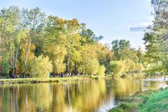 Lake in the city park with walking people Stock Image