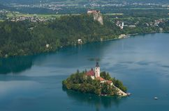 Lake Bled with Island and Castle. In Summer. Small boats can be seen on the lake Stock Photography