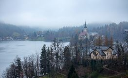 Lake Bled Mist. The Bled chapel and some village houses in the mist behind the trees on a cold morning stock photo
