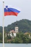 Lake Bled in Slovenia with Cerkev Marijinega Vnebovzetja Church in island and Slovenian flag Stock Photo