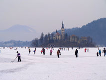 LAKE BLED, SLOVENIA - FEBRUARY 12 2012: Families enjoying a frozen Lake Bled. Lake Bled completely frozen over with families enjoying the winter fun Royalty Free Stock Image