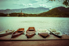 Lake Bled. Summer scene in the park of Bled lake with boats on pier and medieval castle Blejski grad, Slovenia Royalty Free Stock Photo