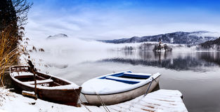 Lake Bled in winter, Bled, Slovenia, Europe. Snowy wooden boats on the backgorund of Church on the Island on Lake Bled, Slovenia, Europe. Winter landscape Bled Stock Photography