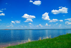 Lake, blue cloudy sky and green grass. Summer landscape with quiet water of lake, blue cloudy sky and green grass Stock Photography