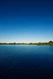 Lake and blue sky. The picture shows a lake and a blue sky stock photos