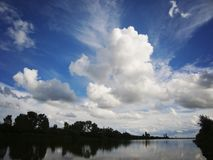 Lake with sky and clouds reflecting in tranquil River. Lake with blue sky and clouds reflecting in tranquil River Stock Photography