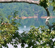 Lake and Boat with Natural Frame. A small boat is seen through the foliage on glassy Carters Lake in the northern Georgia mountains. A tree branch and leaves Stock Images