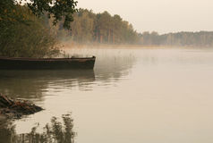 Lake. Boat on the shore of a misty lake on a summer morning Stock Photo