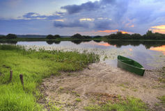 Lake with a boat at sunset. A small lake at sunset Stock Photography