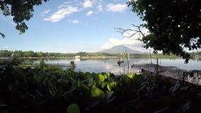 Lake boatman paddles his tiny wooden boat across mountain lake. Sampaloc Lake, San Pablo City, Laguna, Philippines - April 29, 2016: lake boatman paddles his stock footage