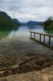 Pier on a calm lake. Dock or pier on a serene, calm lake at the west end of Lake Bohinj (Bohinjsko jezero) in Slovenia royalty free stock image