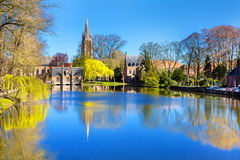 Lake in Bruges, Belgium, church and medieval houses reflection in water Stock Photo