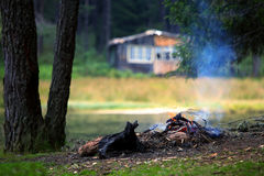 Lake and campfire. Camp fire near lake in autumn time with wooden villa in background Royalty Free Stock Photo