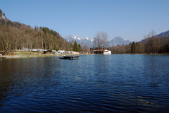Lake and camping in mountains. Small Blue Zellersee Lake with jumping stage and camping at the background of sky and mountains.Chimgauer Alpes Germany Bavaria Royalty Free Stock Photos