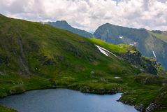 Lake Capra in Fagarasan mountains of Romania. Beautiful summer scenery on a cloudy day. Popular tourist destination for Hiking Royalty Free Stock Photos
