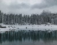 Lake carezza with mountains during a snowy day royalty free stock image