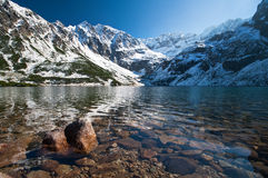 Lake in Carpathian mountains. Scenic view of lake with snow capped Carpathian mountain range in background, Eastern and Central Europe Royalty Free Stock Photo
