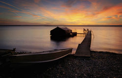 Lake Cayuga Sunrise. A beautiful autumn sunrise on the pebbled shores of Lake Cayuga in the Finger lakes region of New York state. A row boat with oars is docked Stock Photos