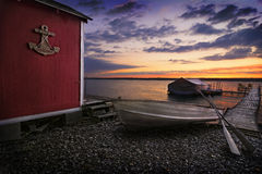 Lake Cayuga Sunrise. A beautiful autumn sunrise on the pebbled shores of Lake Cayuga in the Finger lakes region of New York state. A row boat with oars is docked Royalty Free Stock Images