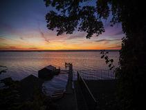 Lake Cayuga Sunrise. A beautiful autumn sunrise on the pebbled shores of Lake Cayuga in the Finger lakes region of New York state. A row boat with oars is docked Stock Photo