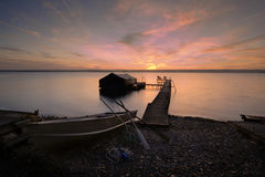 Lake Cayuga Sunrise. A beautiful autumn sunrise on the pebbled shores of Lake Cayuga in the Finger lakes region of New York state. A row boat with oars is docked Stock Image