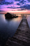Lake Cayuga Sunrise. A beautiful autumn sunrise on the pebbled shores of Lake Cayuga in the Finger lakes region of New York state. A  wooden pier leads out to a Royalty Free Stock Images