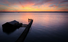 Lake Cayuga Sunrise. A beautiful autumn sunrise on the shores of Lake Cayuga in the Finger lakes region of New York state.  The pier leads out to a power boat Stock Image