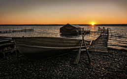 Lake Cayuga Sunrise. A beautiful autumn sunrise on the shores of Lake Cayuga in the Finger lakes region of New York state. A row boat with oars is docked on the Royalty Free Stock Images